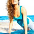 Pretty woman at the beach doing yoga — Stock Photo