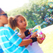Little girl and boy blowing soap bubbles at park — 图库照片