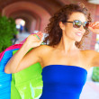 Beautiful smiling young woman with shopping bags wearing sunglasses. — Foto de Stock