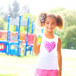 Little African American girl blowing soap bubbles — Stock Photo