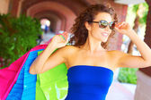 Beautiful smiling young woman with shopping bags wearing sunglasses. — Stock Photo