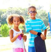 Little girl with push scooter and boy carrying skateboard at park. — Stock Photo