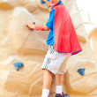 Boy dressed as Superman on climbing wall — Stock Photo