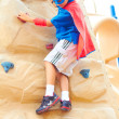 Boy dressed as Superman on climbing wall — Stok fotoğraf