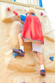 Boy dressed as Superman on climbing wall — Stockfoto