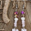 Hnadcrafted earrings on rustic background - Stock Photo