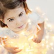 Cute, smiling little girl with glowing Christmas lights — Stock Photo