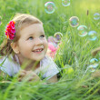 Happy little girl playing with bubbles — Stock Photo