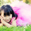 Happy little girl laying on grass in a park - Stock Photo