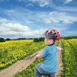 Child cycling on a spring meadow - Foto Stock