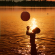 Child playing in water at sunset — Stock Photo