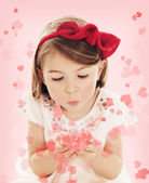 Little girl blowing heart confetti on pink background — Stock Photo