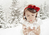 Three years old girl blowing smowflakes in winter landscape — Stock Photo