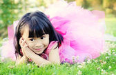 Happy little girl laying on grass in a park — Stock Photo