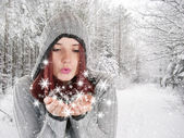 Young woman blowing smowflakes in winter landscape — Stock Photo