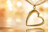 Golden heart on blazing defocused lights background — Stock Photo