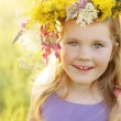Happy little girl in flower crown on sunny summer meadow — Stock Photo