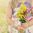 Little girl with flowers on grassy meadow — Stock Photo #29880583