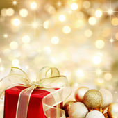 Christmas gift and baubles on defocused lights background — Stock Photo