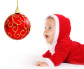 Christmas baby looking at a red ball — Stock Photo