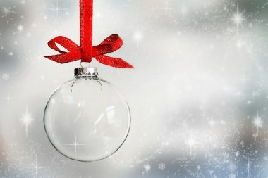 Transparent Christmas ball ornament on snowy background