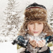 Happy boy blowing snowflakes in winter landscape — Stock Photo