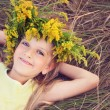 Happy little girl in flowers crown laying on the grass — Stock Photo #32630887