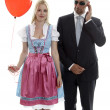 Woman in Dirndl with red heart balloon and Bodyguard - Stock Photo