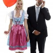 Stock Photo: Woman in Dirndl with red heart balloon and Bodyguard