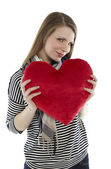 Woman cuddling with a heart pillow — Stock Photo