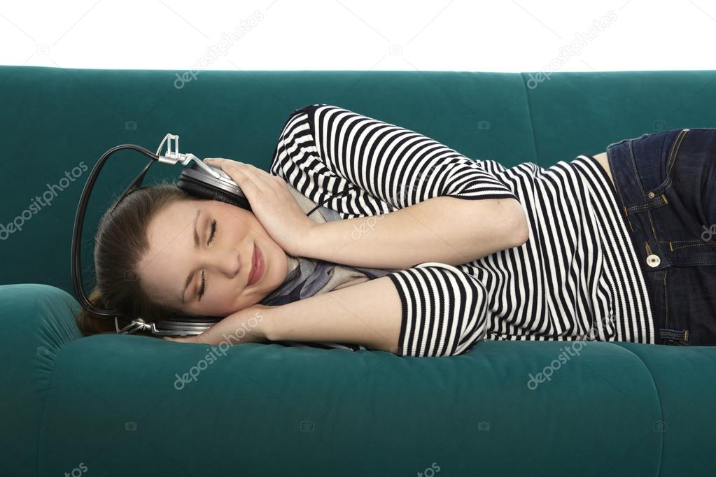 Woman listens to music, while she is lying on a green coach  Stock Photo #19256635