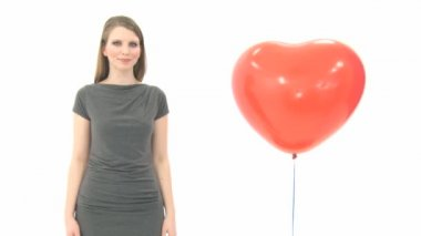 Woman standing next to heart balloon — Stock Video