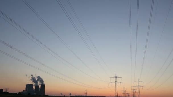 Planta de energía con líneas eléctricas durante la puesta del sol — Vídeo de stock