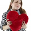 Woman embraces heart pillow — Stock Photo