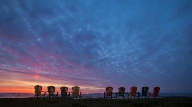 Lever du soleil sur le lac hurton avec groupe de chaises colorées — Vidéo