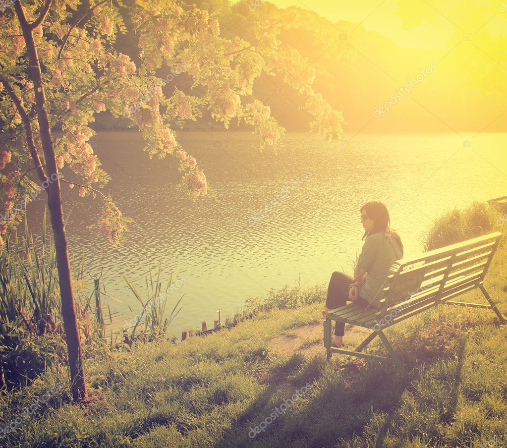 Фотообои Woman with lake in front of her while sitting on a park bench