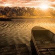 Fishing boat in sunset with background mountains — Stock Photo