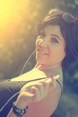 Girl listening music through headphones — Stock Photo