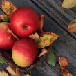 Apple on wooden table with fallen autumn leaves — Stock Photo