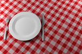 Fork Knife and Plate on a red table cloth — Stock Photo