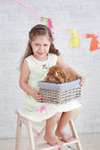 Girl sitting on the ladder with a rabbit — Stock Photo