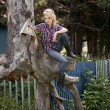 Blonde young country girl sitting on large old stump — Stock Photo