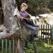 Blonde young country girl sitting on large old stump — ストック写真
