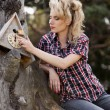 Blonde young country girl sitting on large old stump — Stock Photo #30086059