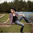 Young girl wearing jeans and checkered shirt sitting on the fence — ストック写真