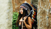Native american, indians, in traditional dress with decorative black ax, stands between two stones — Foto de Stock