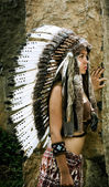 Native american, Indians in traditional dress, standing in profile next to the stone slabs. American indian Girl — Stockfoto