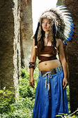 Native american, indians, in traditional dress stands tall in a grove of stone — Foto de Stock