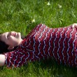 Dreaming pregnant girl lies on a grass — Stock Photo