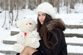 Cheerful Caucasian Young Woman in Snowy Weather holds a toy — Stockfoto